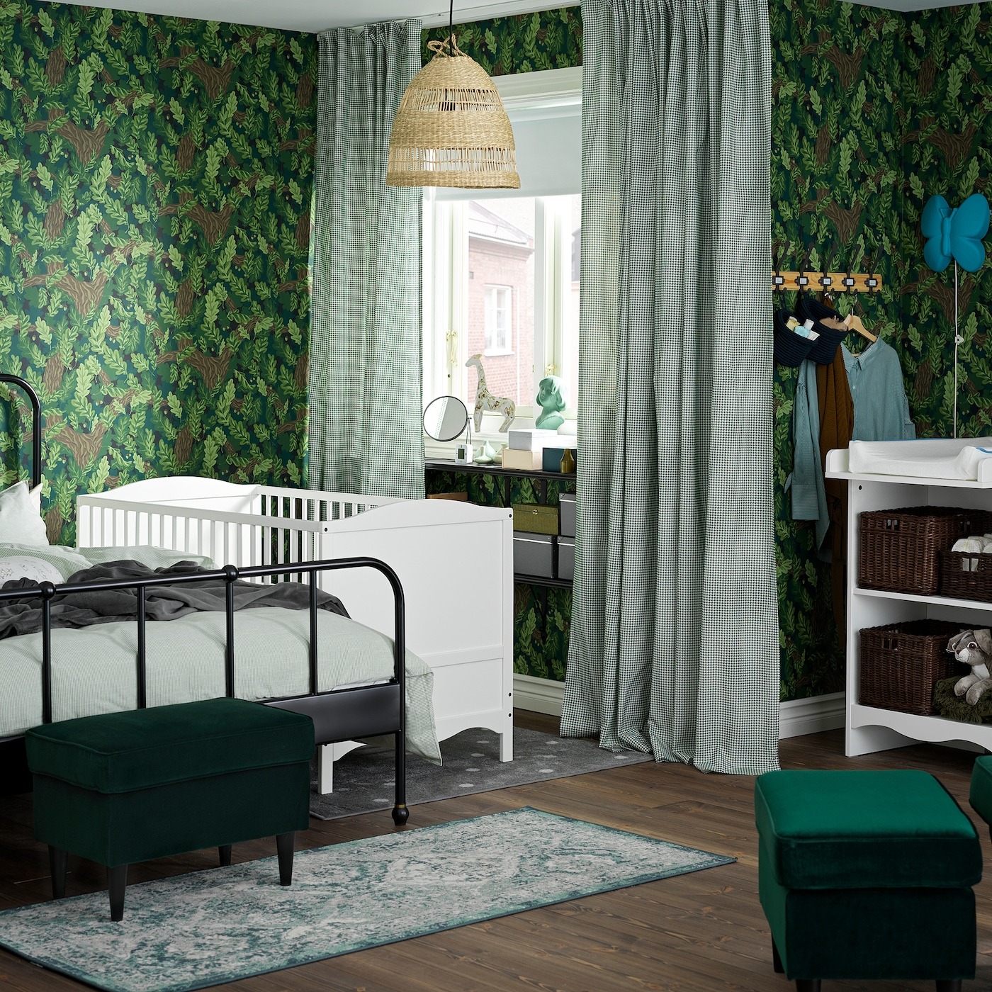 Zelena spavaća soba/dečja soba sa stolom za povijanje i krevecem u beloj boji, crnim krevetnim okvirom i belim/zelenim zavesama.