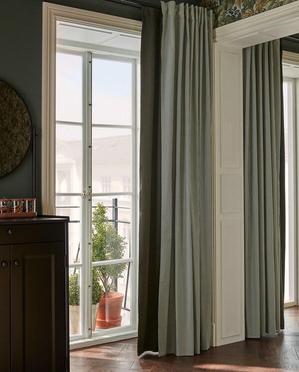 Zelena zavjesa za zamračivanje i zavjesa s uzorkom vise pokraj balkonskih vrata i pružaju prilagođenu razinu svjetlosti i privatnosti.