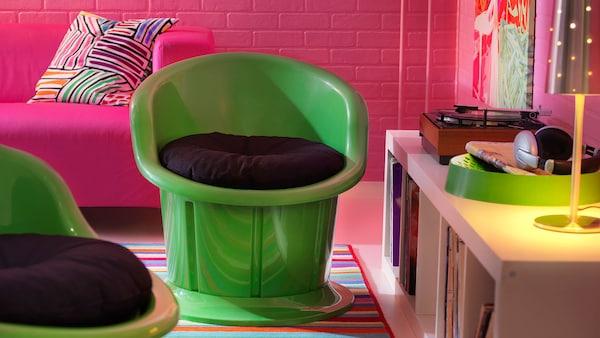 Zelené plastové křeslo POPPTORP postavené na barevném koberci.