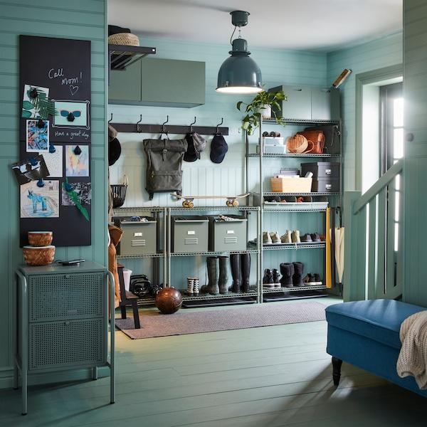 Zeleni hodnik sa sistemom za odlaganje, ormarić montiran na zid, kutije i fiokar u sivim i zelenim nijansama, kao i tepih u tamnosivoj boji.