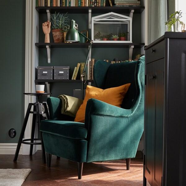 Zeleni STRANDMON naslonjač pokraj polica s knjigama, zelene podne lampe, crnog elementa i crne barske stolice.