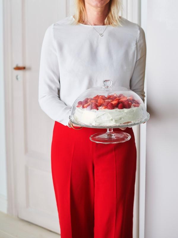 Žena drží sklenený servírovací podnos ARV BRÖLLOP s vrchnákom, na ktorom je jahodový koláč.