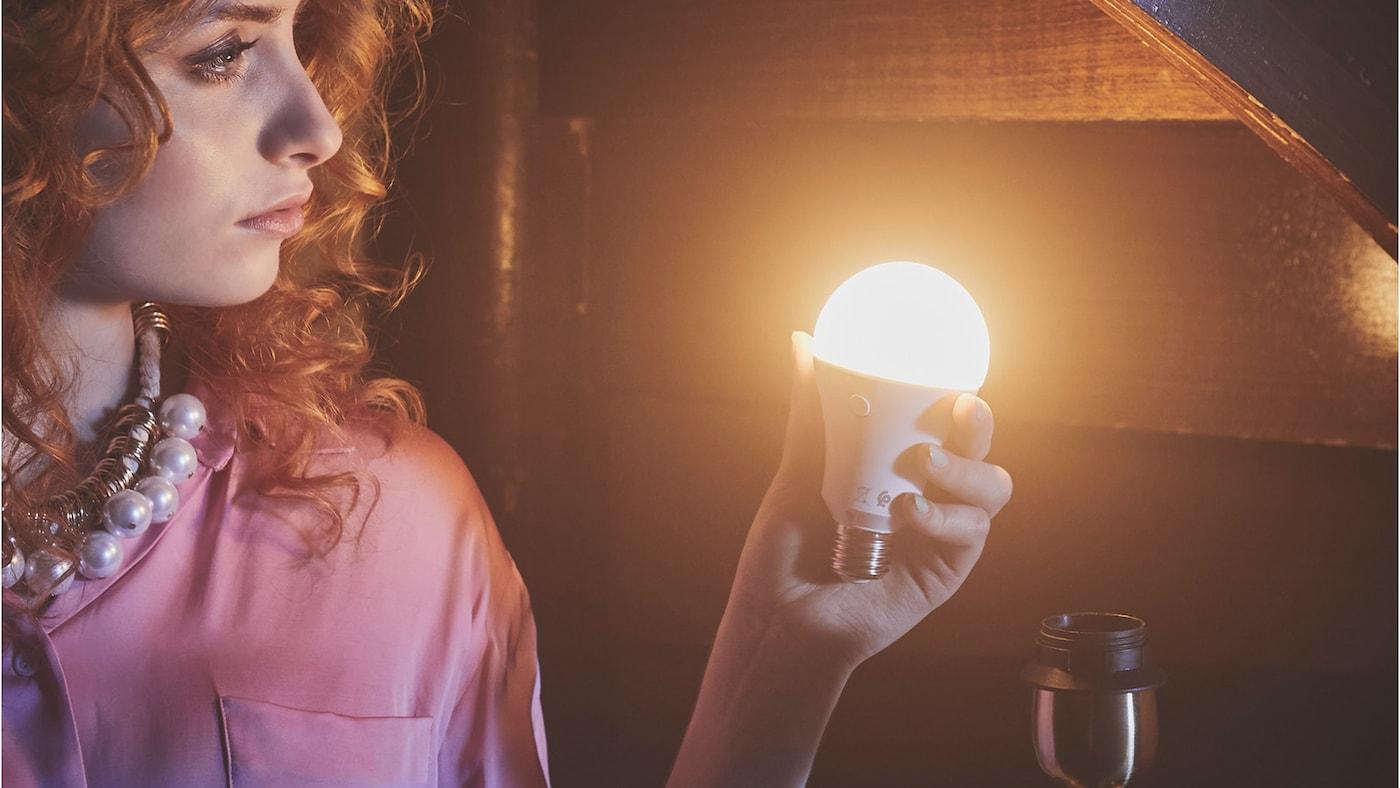 Žena drží v ruce rozsvícenou žárovku.