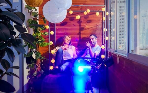 Žena i muškarac sede na balkonu na SVANÖ drvenoj klupi s upaljenim filmskim projektorom na pomoćnom stočiću ispred.