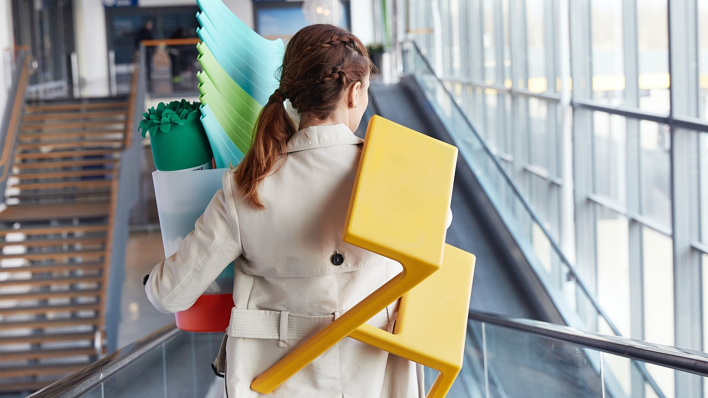 Žena jede dolů po eskalátorech s výrobky IKEA.