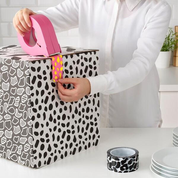 Žena koristi roze i žutu OMBYTE traku da zatvori tufnastu OMBYTE kutiju na beloj površini.