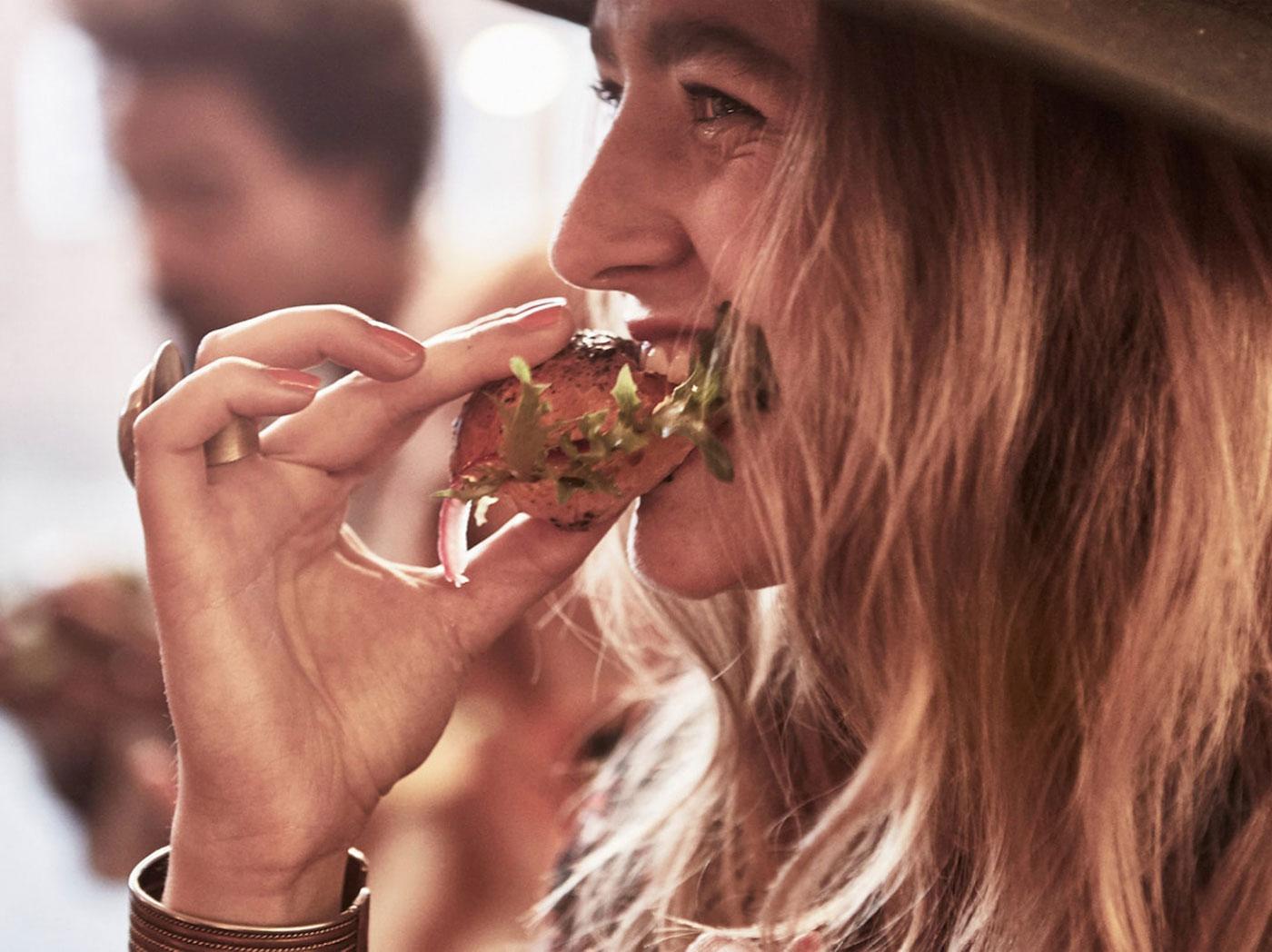 Žena, která jí housku se salátem.
