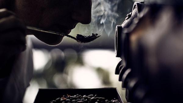 Žena, která zkoumá vůni kávových zrn na lžičce.