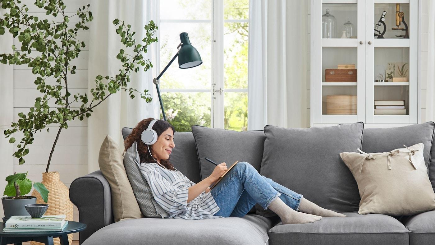 Žena ležící na pohovce se sluchátky na uších, poslouchá hudbu a hraje si na tabletu