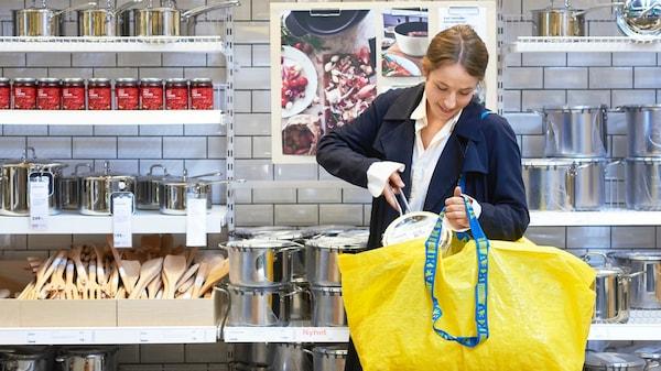 Žena nachádzajúca sa v obchode IKEA, ktorá s úsmevom vkladá výrobok do žltej tašky IKEA.