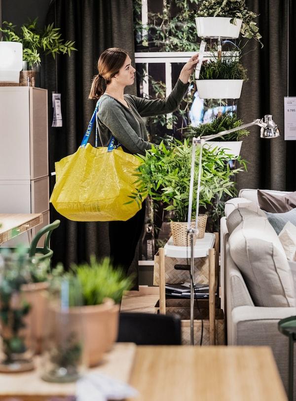 Žena nakupujúca v obchodnom dome IKEA so žltou taškou.
