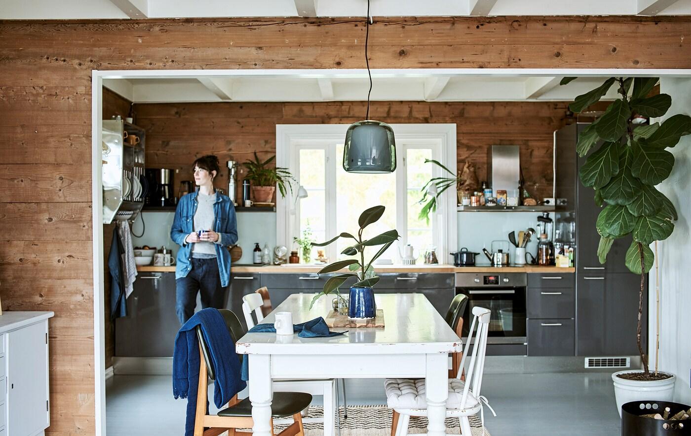 Žena naslonjena na sjajni sivi element u uskoj kuhinji koja se otvara prema blagovaonici s bijelim drvenim stolom i stolicama.