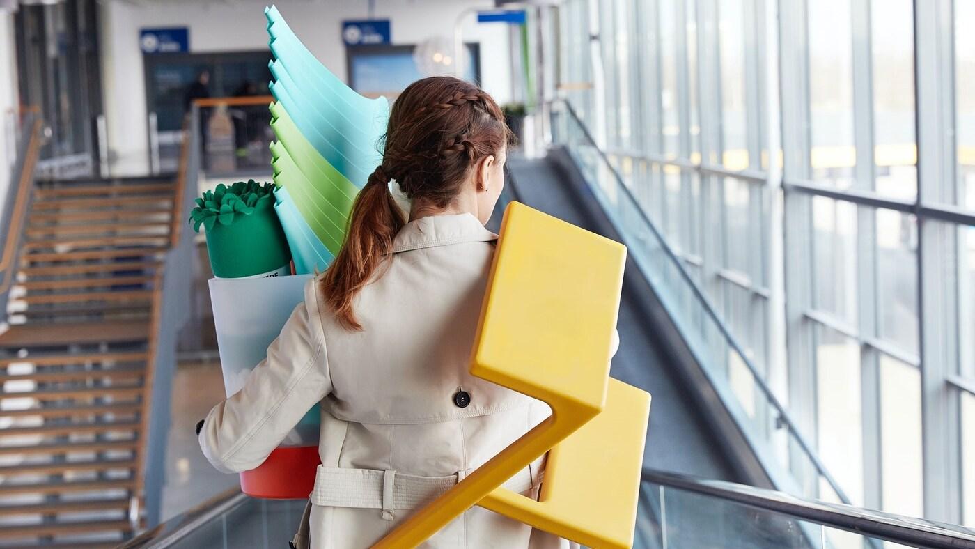 Žena odcházející z IKEA držící žluté schůdky a velký nákup