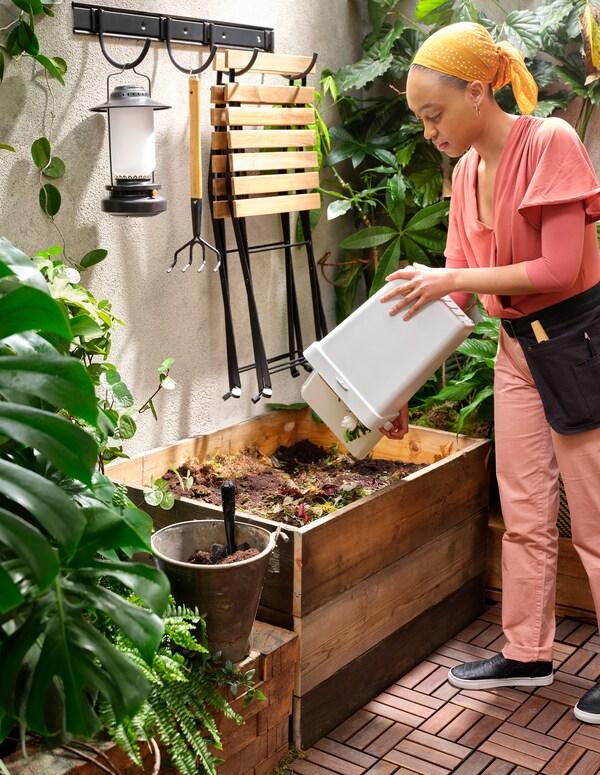 Žena prazni belu HÅLLBAR kantu s prehrambenim otpadom u sanduk za kompost, u malom dvorištu s drvenim letvama, s puno biljaka.