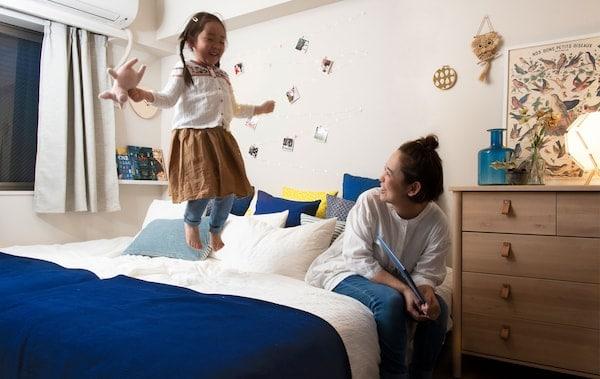 Žena sedí a dieťa stojí na veľkej posteli v bielej spálni s nástennou knižnicou.