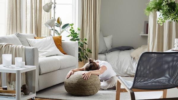 Žena sedí na koberci v obývacím pokoji v tureckém sedu a drží se sedátka, vedle je bílá pohovka, stolek a šedé křeslo.