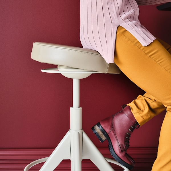 Žena sedí na stoličce bez opěrky.