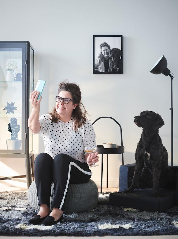 Žena sedi u dnevnoj sobi na SANDARED tabureu, slika selfi na kojem su ona i njen crni pas koji sedi pored.