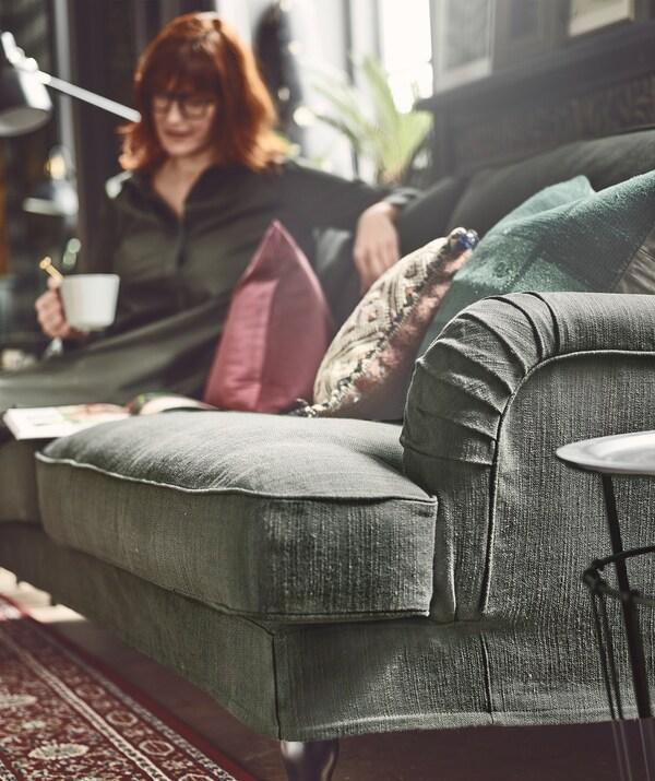 Žena sedi u opuštenoj pozi na kraju sofe, blizu prozora, drži šolju i gleda otvorenu knjigu.
