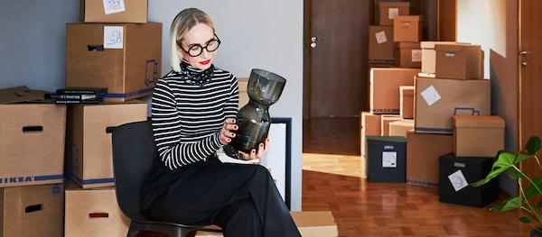 Žena sedí v místnosti plné krabic na stěhování a v rukou drží a obdivuje vázu.