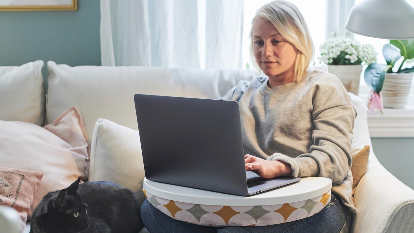 Žena sediaca za počítačom v pohodlí domova.