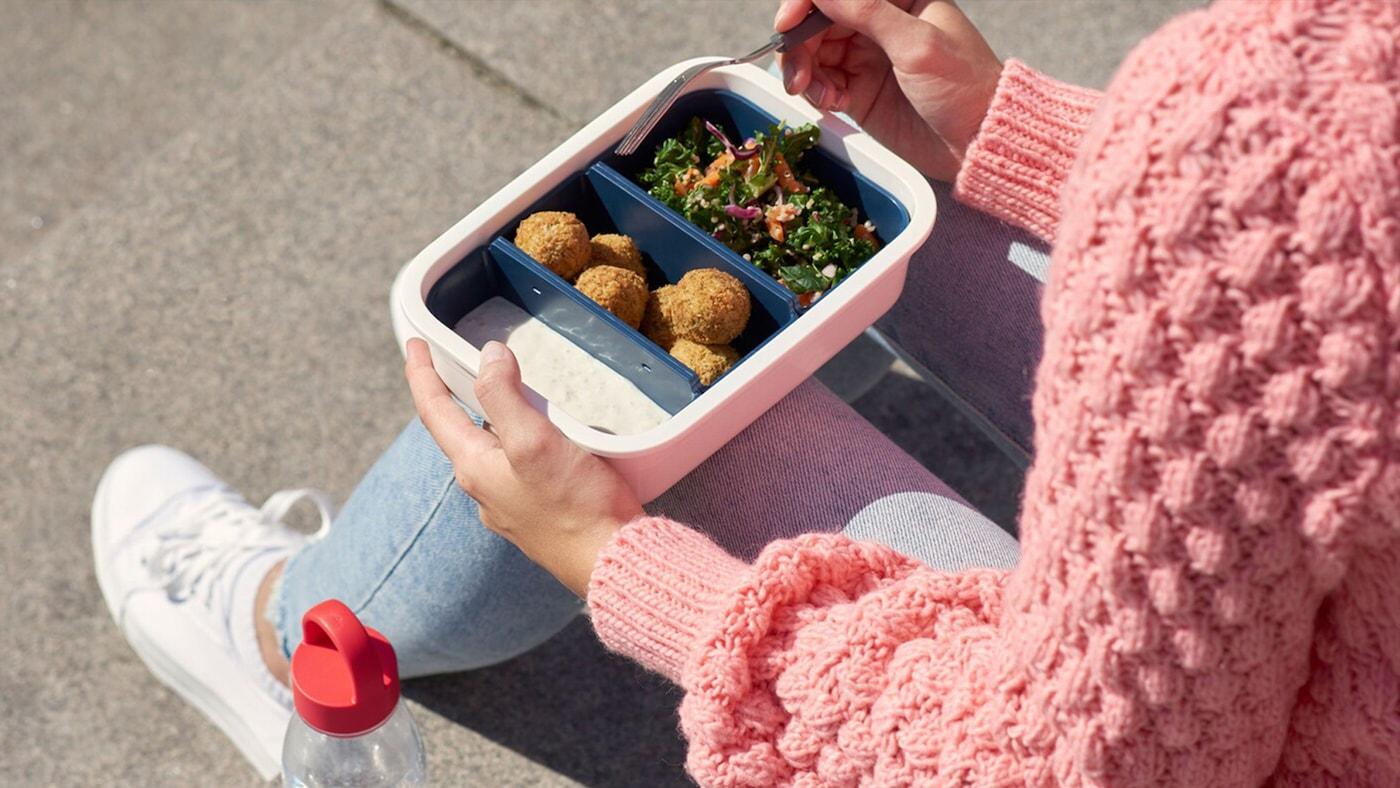 Žena sedící na schodech a jí připravené jídlo z krabičky.
