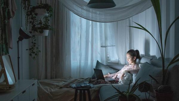 Žena sedící v pohodlí domova ve tmě se účastní Hodiny Země.