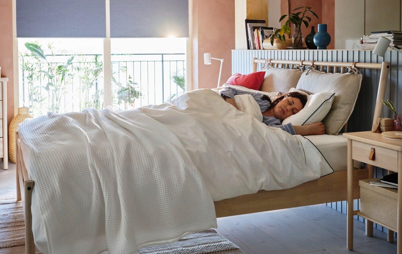 Žena spí v posteli BJÖRKSNÄS, oknem za postelí prosvítá sluneční světlo