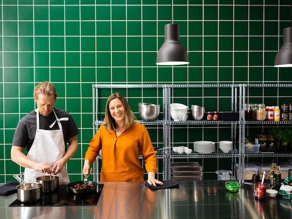 Žena stojí v kuchyni z nehrdzavejúcej ocele so zeleným obkladom na stene a drží panvicu s bezmäsitými guľôčkami.