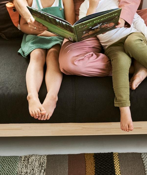 Žena u roze kombinezonu sedi na sivoj i drvenoj sofi s rukama oko dečaka i devojčice, i čita knjigu za decu.