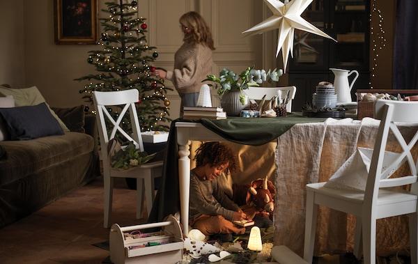 Žena ukrašava novogodišnju jelku, a ispred jelke nalazi se sto ispod kojeg se dečak igra svojim igračkama, poluskriven.