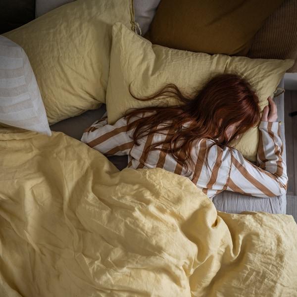 Žena v pruhovaném pyžamu spící na posteli se žlutým povlečením a hnědými a bílými polštáři navíc.
