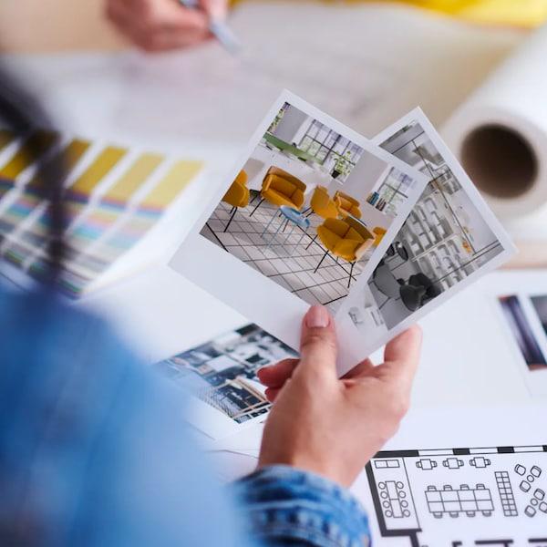 Žena v ruce drží fotky koláží pro vybavení kanceláře.
