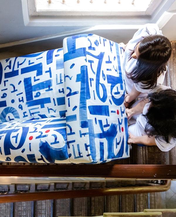 Žene na stepeništu, pored prozora, drže krajeve plave i bele platnene sofe koju nose.
