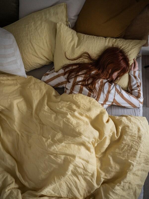 Žene u prugastim pidžamama spavaju dubokim snom u krevetu na kojem se nalazi svijetložuta PUDERVIVA navlaka i jastučnica.
