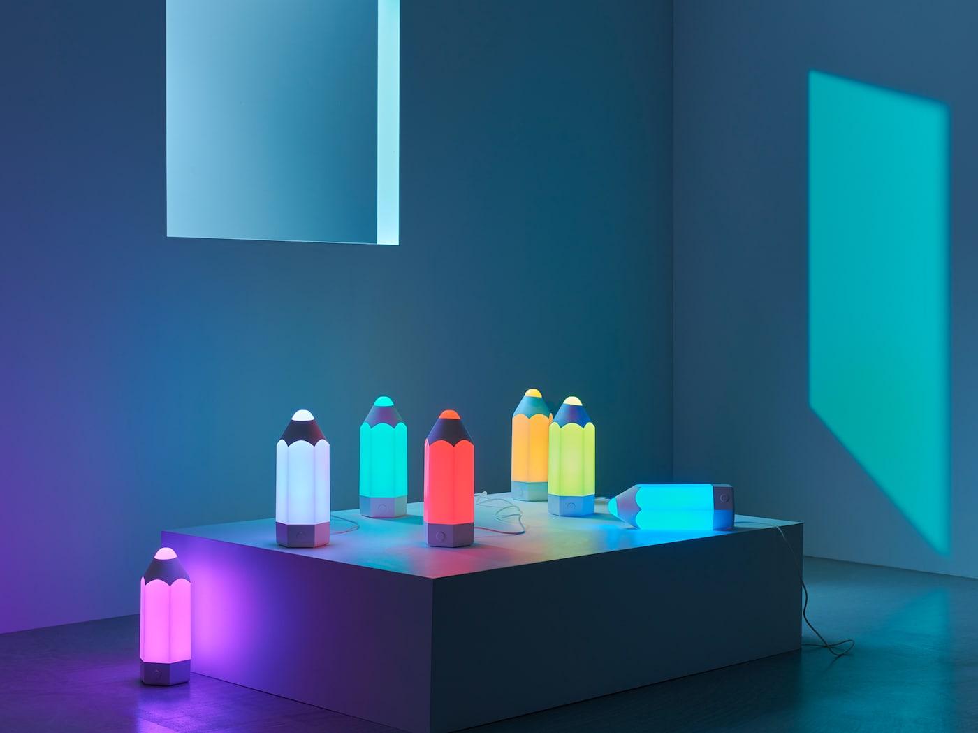 Zeven speelse PELARBOJ tafellampen in de vorm van een potlood, in de zeven beschikbare lichtkleuren.
