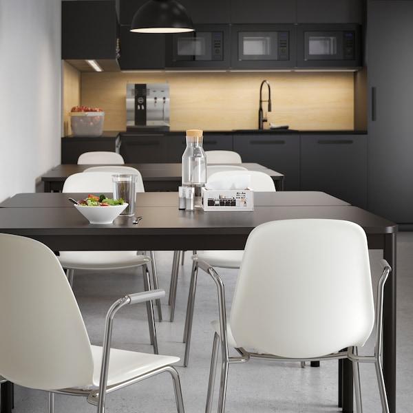 Zgrupowane w dwóch miejscach antracytowe stoły kuchenne z białymi krzesłami, ustawione w kuchni z prostymi, antracytowymi frontami szafek.