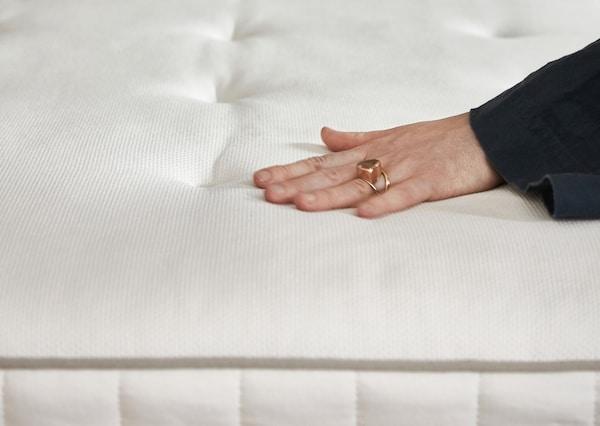 Женщина проверяет рукой степень жесткости матраса ХОККОСЕН