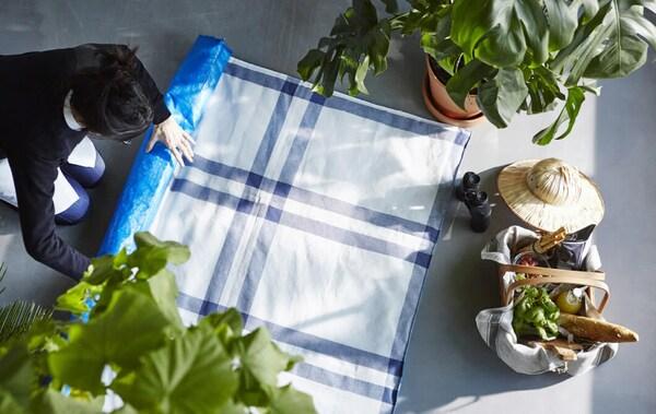 Женщина расстилает плед для пикника, сделанный из синих сумок ИКЕА и кухонных полотенец
