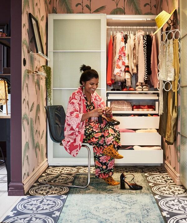 Женщина сидит на стуле в красочном помещении, которое напоминает нишу, оборудованную полуоткрытым шкафом с раздвижными дверями; на стене висят аксессуары.
