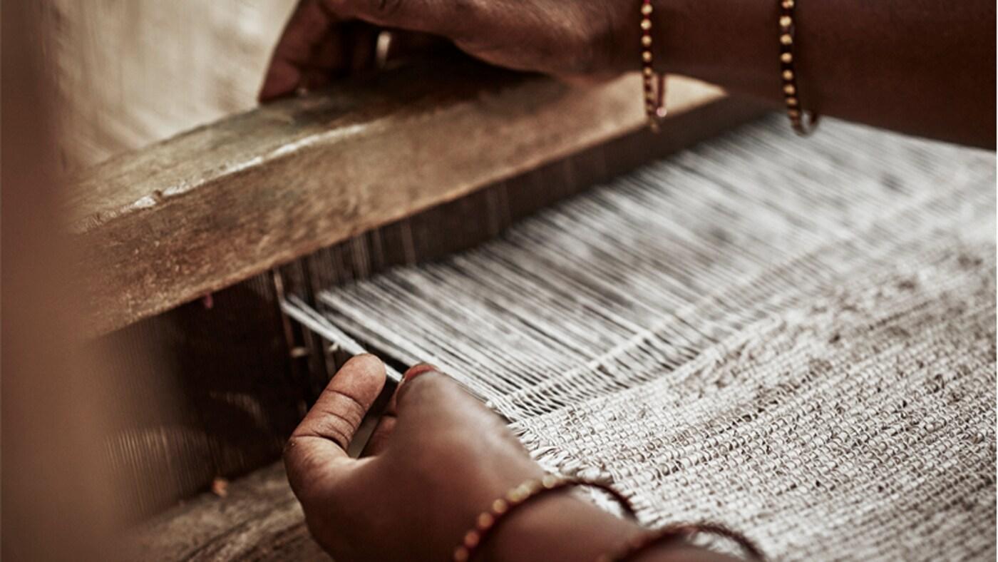 Женщина вручную плетет бежевый текстиль. На руках у нее золотые браслеты.