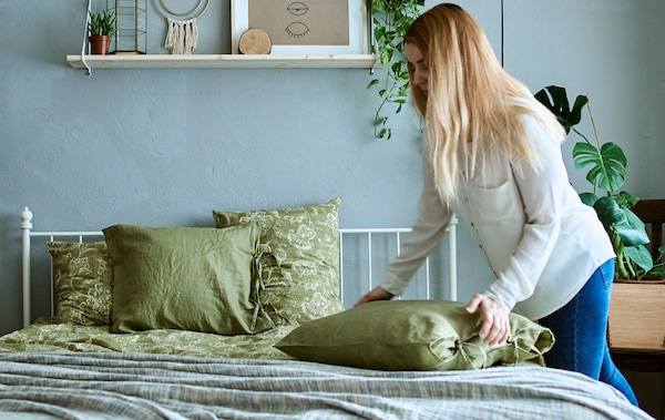 Жінка у спальні з інтер'єром у сіро-зелених кольорах, наповненій кімнатними рослинами, підбиває подушку на ліжку, застеленому зеленою постільною білизною.