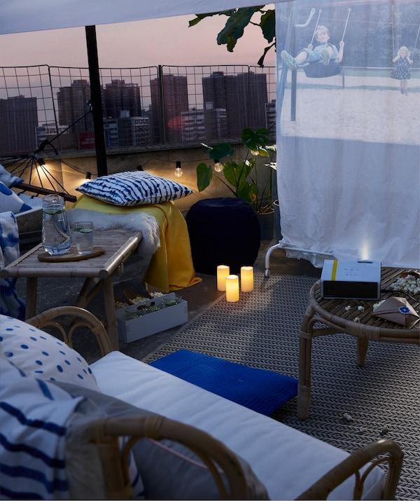 Журнальный столик с попкорном, окруженный пуфами, садовые кресла и гамак напротив экрана на крыше.