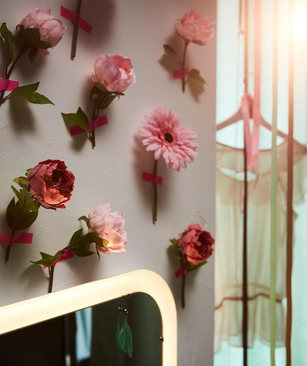Zid prekriven SMYCKA veštačkim cvetovima, zasebno zakačenim roze trakom.