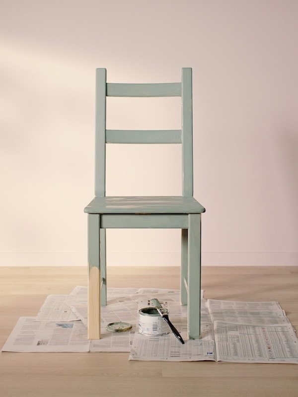 Židle IVAR natíraná světle zelenou barvou stojící na starých novinách v prázdné místnosti se světlou dřevěnou podlahou a světle růžovými stěnami.