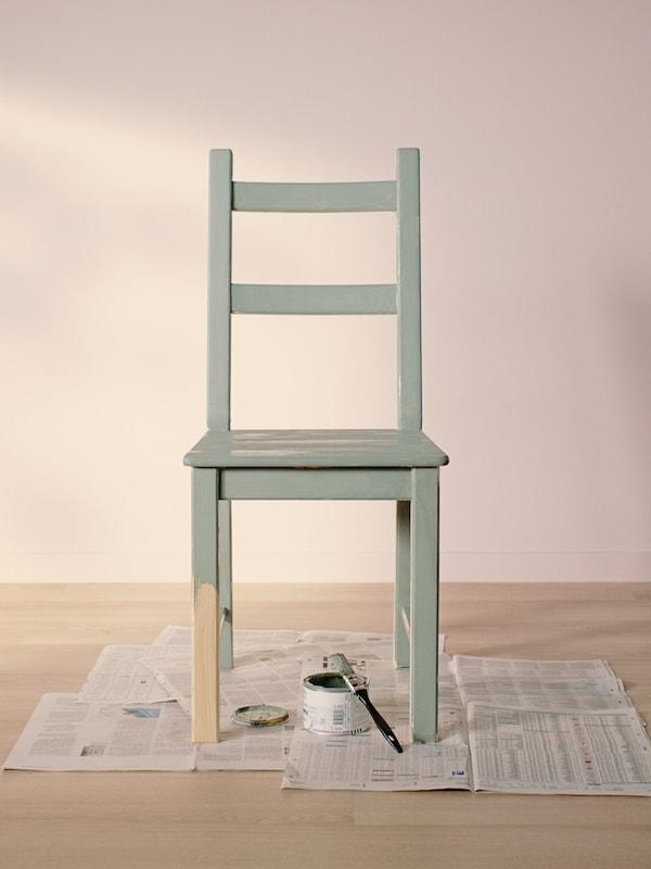 Židle IVAR postavená na starých novinách,  plechovka s barvou a štětec. Židle je zpola natřená zelenkavou barvou.