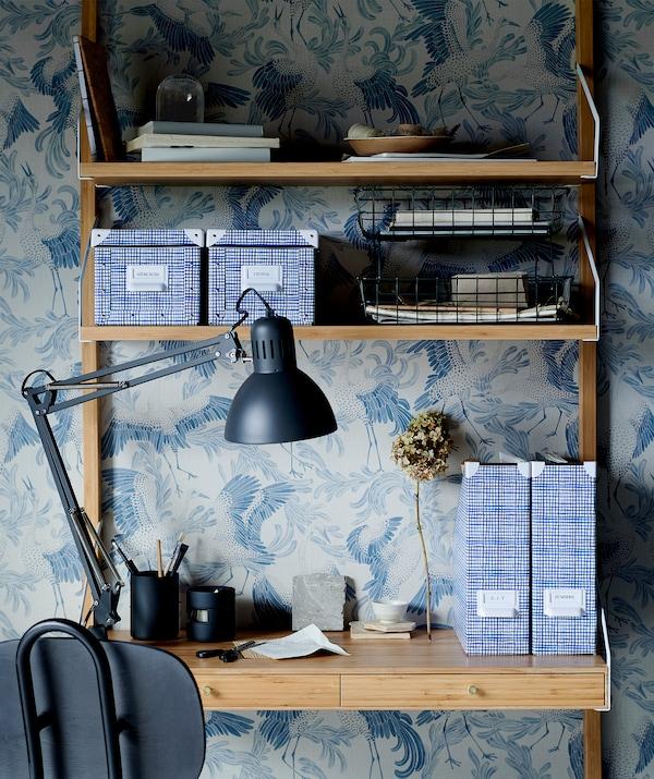 Zidne police koje služe kao mala kućna kancelarija; razni elementi za odlaganje, lampa na radnom stolu, kancelarijska stolica, grafička tapeta.