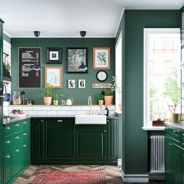 Zielona kuchnia BODBYN, dywan na podłodze, kolekcja obrazków na na ścianie.