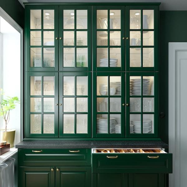 Zielona kuchnia ze szklanymi drzwiami do szafek z białymi talerzami wewnątrz. Otwarta szuflada, w której widać wewnętrzne oświetlenie.