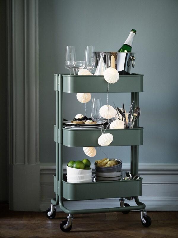 Zielony wózek RÅSKOG załadowany przygotowanymi na imprezę kieliszkami, naczyniami i napojami.